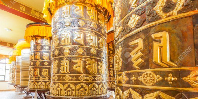 20562537-Buddhist-prayer-wheels-in-Tibetan-monastery-with-written-mantra-Yoksom-Sikkim-India--Stock-Photo