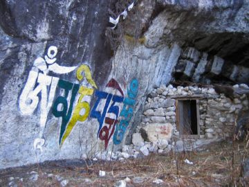 A small retreat cave with Om Mani Padme Hum written on the rock in front. Lapchi, South Central Tibet.
